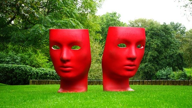 large red tragedy comedy masks on lawn in garden