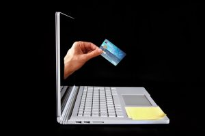 hand with credit card coming out of notebook computer screen