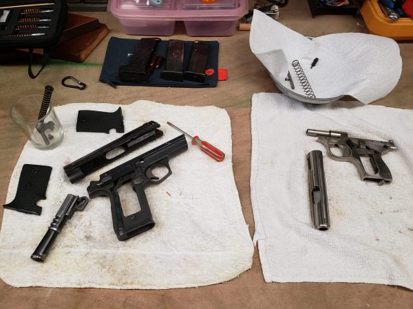 Fivestar 9mm and sterling 25 25 acp pistols on work bench for restoration